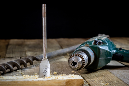 Old good carpentry, tools drill bit. Wooden carpentry table and old good carpentry tools on it. Black background. Stock Photo