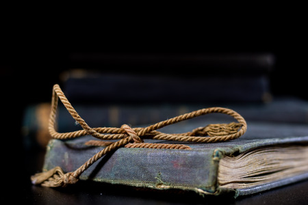 An old book lying on a black table. In the background a pile of old chunks. Black table, black background.