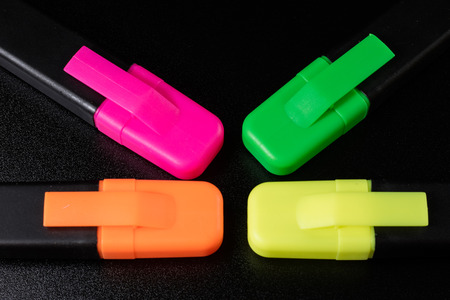 highlighter pen: Office Highlighter on a black background. Office Mazak to draw are lying on a black countertop. Black background.