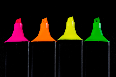Office Highlighter on a black background. Office Mazak to draw are lying on a black countertop. Black background.