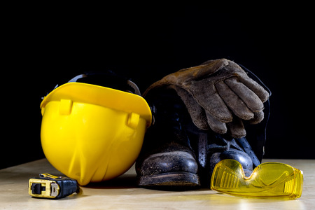 Workwear, helmet, gloves and glasses on a wooden working table. Place workshop, black background.