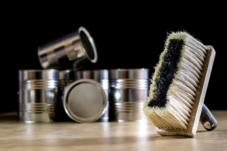 hair roller: Cans of paint on a wooden workshop table. Next to the pedals and paint rollers. Black background