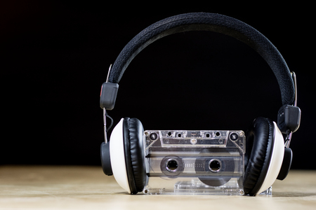 Cassette tape and headphones for listening to music. Old good music from the 80s. Wooden table, black background