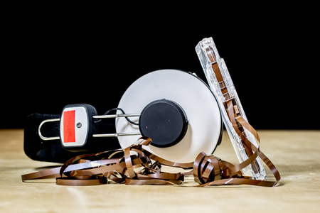 grabadora: Cassette tape and headphones for listening to music. Old good music from the 80s. Wooden table, black background