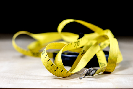 Tape for measuring in the field. A measure tangled on a wooden table. Black background