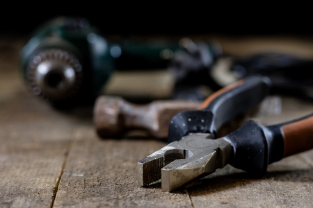 Tools in the workshop. Tools, hammer, drill, drill on a wooden table. black background