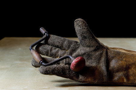 Hand in glove with a tool for work in the workshop. Hand protected by working coat. Workshop tool. Black Stock Photo