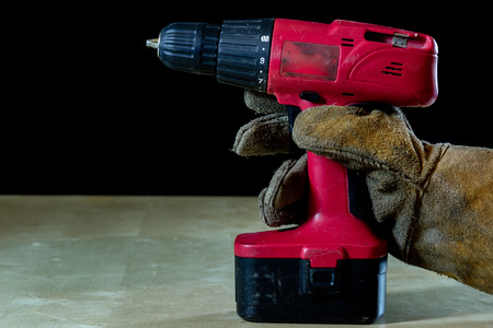 Hand in glove with tool for work in workshop. Hand protected by working coat. Workshop tool. Black background.
