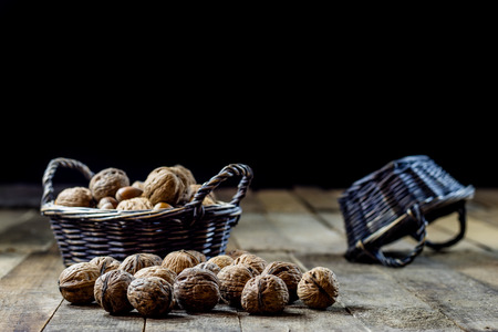 Tasty walnuts in a basket on a kitchen table. Autumn season. Wooden table, black background Stock Photo