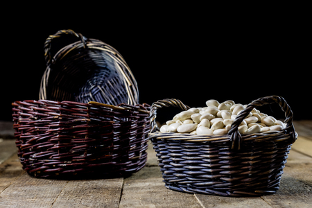 haricot: Tasty beans in a basket on a kitchen table. Autumn season. Wooden table, black background Stock Photo