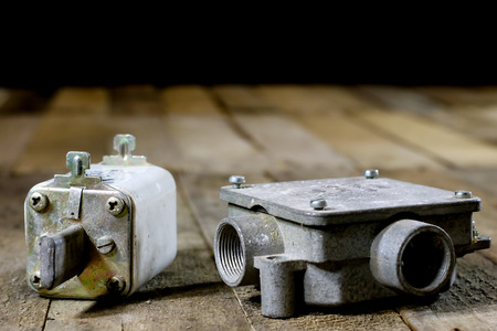 Old ceramic fuse holders. Old electrical accessories. Wooden table, black background