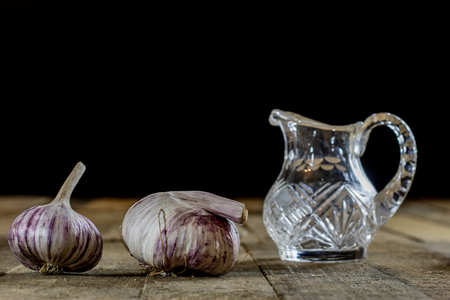 Tasty garlic on a wooden kitchen table. Vegetables in the kitchen atmosphere. Wooden table, black background. Stock Photo