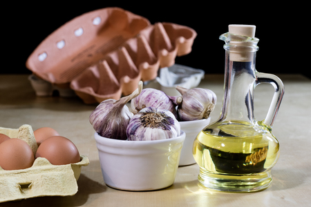 Garlic, eggs and oil on a wooden kitchen table. Kitchen with products for food preparation. Black background