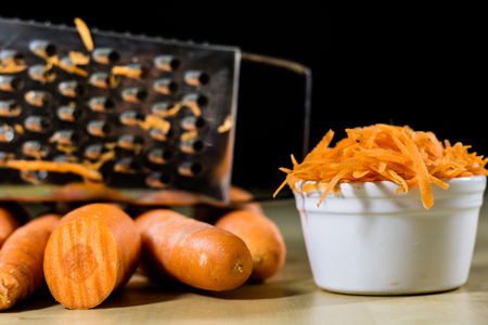 Carrot on the kitchen table. Vegetable grater. Kitchen table.