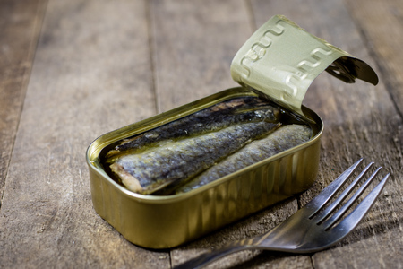 A tin can of fish on a wooden kitchen table. Next to the can fork. Preserved fish in a tin. Old kitchen, black background.
