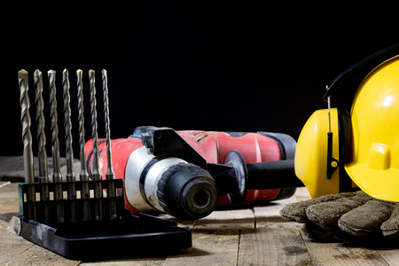 Safety accessories and impact hammer. Accessories for a builder on a wooden table. Black background.
