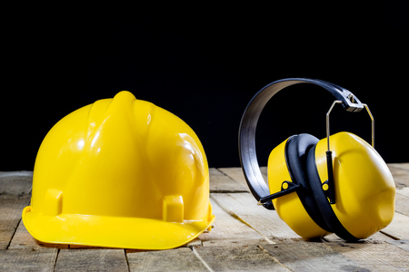 보호 복, 헬멧, 장갑 및 안경. 청력 보호 장치. 나무 테이블에 안전 액세서리입니다. 검정색 배경입니다.