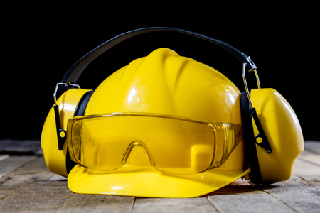 Protective clothing, helmet, gloves and glasses. Hearing protectors. Safety accessories on a wooden table. Black background.