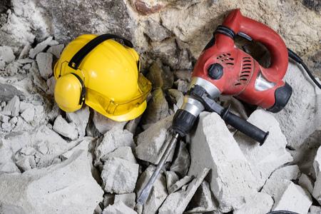 Demolición de muros. Casco de martillo eléctrico y protección auditiva sobre los escombros. Ladrillo viejo y muro de construcción remodelado. Grunt en el fondo de la antigua muralla.