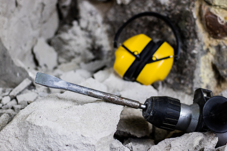 Demolition of walls. Electric hammer helmet and hearing protection lying on the rubble. Old brick and remodeled building wall. Grunt on the background of the old wall. Standard-Bild