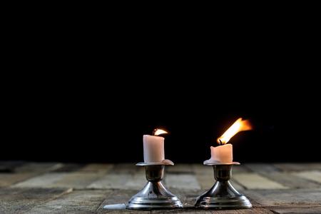 Candele soffiate in candelabri d'argento con stoppino affumicato. Fumo da uno stoppino su uno sfondo nero. Tavolo di legno