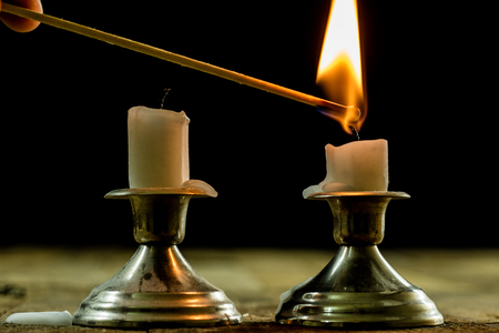 shabat: candles burning in candlesticks on a wooden table. Silver candlesticks. Black background