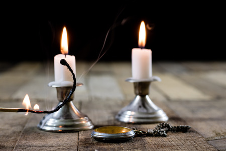 shabbat: candles burning in candlesticks on a wooden table. Silver candlesticks. Black background