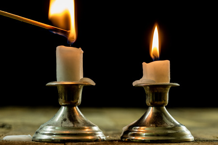 candles burning in candlesticks on a wooden table. Silver candlesticks. Black background