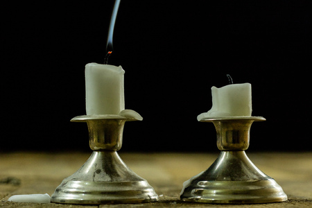 Blown candles in silver candlesticks with smoked wick. Smoke from a wick on a black background. Wooden table