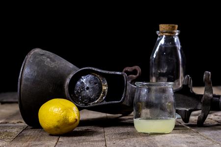 old cast iron juice machine on a wooden kitchen table. Lemon juice and squeezed lemon. Black background