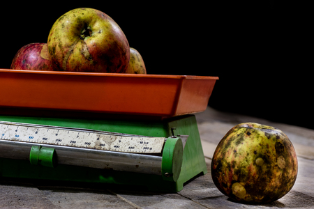 weigh machine: tasty apples and old kitchen scales on a wooden table. Kitchen scale with scale. Black background. Stock Photo