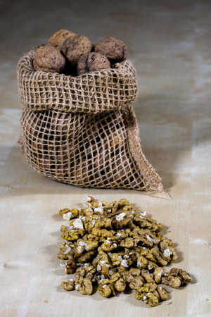 Fresh nuts in a jute bag on a wooden kitchen table. Italian hazelnuts in the kitchen before Christmas. Black background