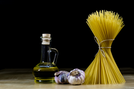 Pasta and olive oil on an old kitchen table. Recipes in old books in the kitchen on a wooden table. Black background.