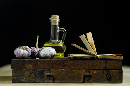 Old books and spices. Dried garlic and recipes. Old kitchen table. Black background Stock Photo