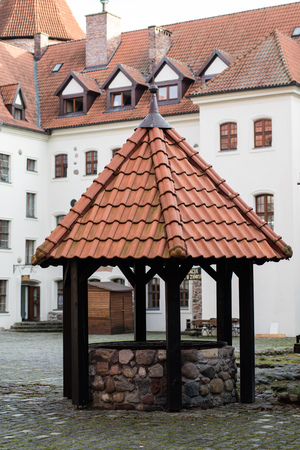 Teutonic castle and red brick tower in the park in the autumn season. A high tower with a sloping red brick roof on a hill. Autumn season