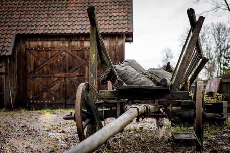 Old ladder car on the yard in a farm yard. Wooden cart with wooden wheels. Bags loaded onto the cart. Stock Photo