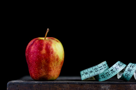 Tasty apple on an old dark wood table. Tape measure next to tasty fruit. Fruit on a diet. Black background Stok Fotoğraf