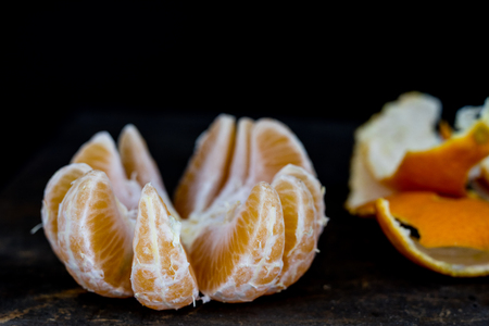 Tasty mandarin on an old dark wooden kitchen table. Peeled tangerine and shells in the distance on the table. Black background Stock Photo
