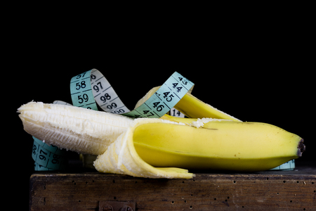 Peeled banana and measure tailor on an old kitchen table. Fruit and kitchen measure. Black background.