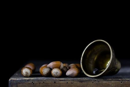 Nuts in a natural bag. A bag of nuts and a bell on an old dark wooden table. Black background Stock Photo