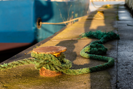 Bollard in the fishing port on the wharf. The wrapped rope mooring fishing boats in the sea port. Autumn season