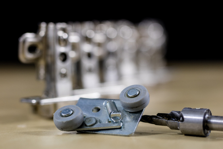 Carpentry tools and accessories on a workshop table. Hinges and screws together with the screwdriver in the workshop. Black background. Stock Photo