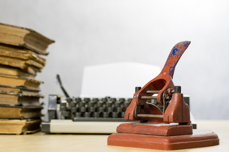 Old office paper punch on a wooden table. Office accessories on the background of an old typewriter. Baiłe background.