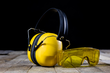 Protective clothing on a wooden workshop table. OSH accessories in the workshop. Black. background. Stock Photo