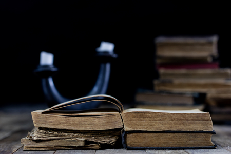 Old destroyed books on a wooden table. Reading room library with very old books on a wooden table. Black background. Stock Photo