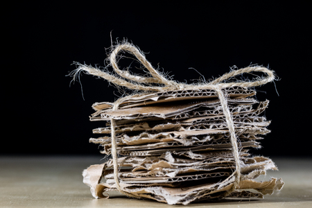 Cardboard pieces stacked and tied with a jute string. Waste paper packed in cubes and tied with a string. Black background.