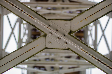 Steel construction, lattice connected by an old method for rivets. Truss in the old bridge connected by rivets on the river. Winter scenery. Archivio Fotografico