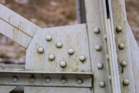 Steel construction, lattice connected by an old method for rivets. Truss in the old bridge connected by rivets on the river. Winter scenery. Stockfoto