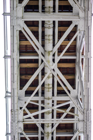 Steel construction, lattice connected by an old method for rivets. Truss in the old bridge connected by rivets on the river. Winter scenery. Banco de Imagens