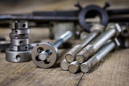 Metalwork tools on the workshop table. Threading dies and taps in an old dusty workshop.